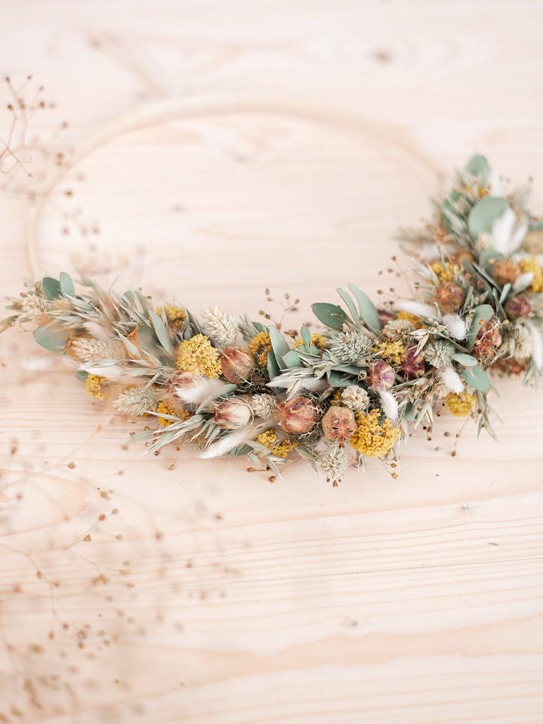 Loopkranz aus Trockenblumen auf Holzring liegt auf dem Tisch