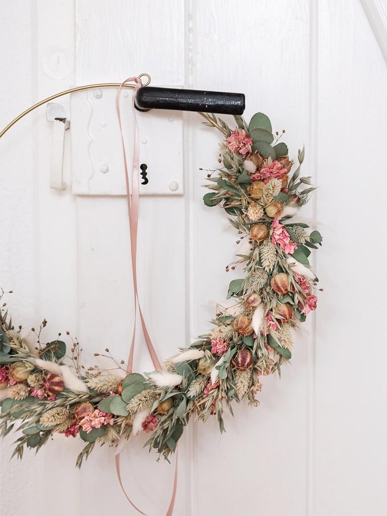 Selbstgebundener Loopkranz aus Trockenblumen hängt an einem Türgriff